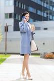 Happy businesswoman calling on smartphone in city Stock Photos
