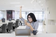 Happy businesswoman celebrating her success. Happy businesswoman raising her hand to celebrating success while reading good news on the smartphone Royalty Free Stock Image