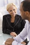 Happy businesswoman chatting with businessman Stock Images