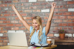 Happy businesswoman cheering in office Royalty Free Stock Photos
