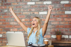 Happy businesswoman cheering while sitting in office. Happy businesswoman cheering while sitting in front of laptop in office Royalty Free Stock Photos