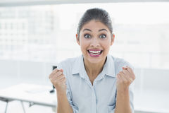 Happy businesswoman clenching fists in office Royalty Free Stock Photography