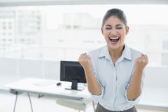 Happy businesswoman clenching fists in office Royalty Free Stock Images