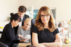Happy businesswoman with colleagues in the background Stock Images