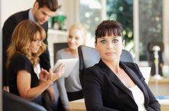 Happy businesswoman with colleagues in the background Royalty Free Stock Photo