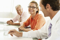 Happy Businesswoman With Colleagues In Conference Room Stock Photo