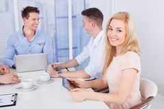 Happy businesswoman with colleagues in conference room Royalty Free Stock Image