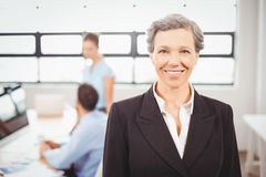 Happy businesswoman with colleagues working in background Stock Photography