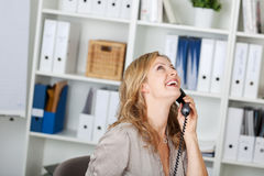 Happy Businesswoman Communicating On Phone. Portrait of happy businesswoman communicating on land line phone at office royalty free stock photography