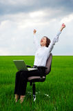 Happy businesswoman with computer. Sitting on chair over green field Royalty Free Stock Images