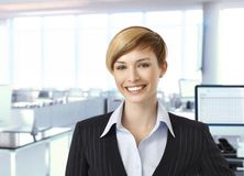 Happy businesswoman in corporate office Royalty Free Stock Images