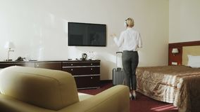 Happy businesswoman dancing and singing while listening music on wireless headphones while have fun walking at hotel. Happy cheerful businesswoman dancing and stock footage