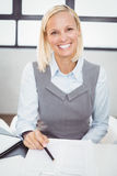 Happy businesswoman with documents sitting at desk Royalty Free Stock Image