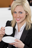Happy Businesswoman Drinking Coffee In An Office Royalty Free Stock Images