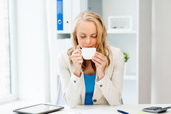 Happy businesswoman drinking coffee at office Royalty Free Stock Photos