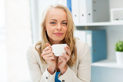 Happy businesswoman drinking coffee at office Royalty Free Stock Images
