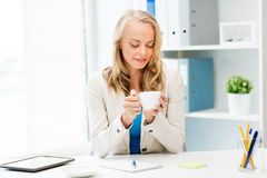 Happy businesswoman drinking coffee at office Stock Images