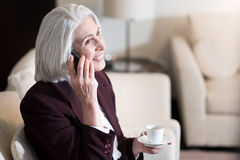 Happy businesswoman drinking coffee and talking on the phone Royalty Free Stock Photo