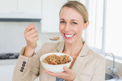 Happy businesswoman eating cereal before work in the morning Royalty Free Stock Photo