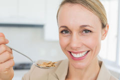 Happy businesswoman eating cereal before work in the morning Stock Images