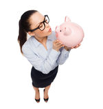 Happy businesswoman in eyeglasses with piggy bank Stock Image