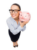 Happy businesswoman in eyeglasses with piggy bank Royalty Free Stock Photos