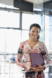 Happy Businesswoman With File Folder In Office Royalty Free Stock Photography