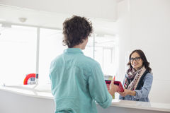Happy businesswoman giving files to male colleague at counter in creative office Royalty Free Stock Photo
