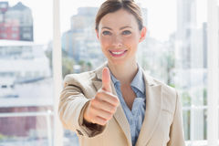 Happy businesswoman giving thumb up to camera Stock Photos