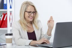 Happy businesswoman with glasses working, chating with laptop at office. Happy businesswoman with glasses working and chating with laptop at office royalty free stock image