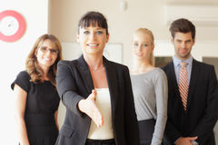 Happy businesswoman going to shake your hand Stock Image