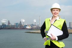 Happy businesswoman in hardhat and safety vest standing outdoors with clipboard Stock Photo