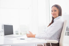 Happy businesswoman having coffee at her desk Stock Images