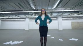 Happy businesswoman having fun. Lady in a suit is dancing after throwing papers in an empty hall stock video