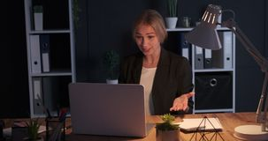 Businesswoman having late night video call at office. Happy businesswoman having late night video call using laptop at office stock footage