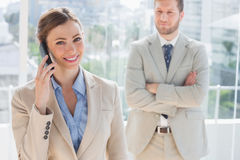 Happy businesswoman having phone conversation. With colleague behind her Royalty Free Stock Photo