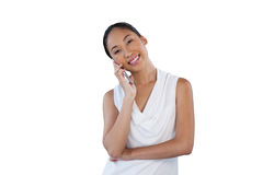 Happy businesswoman with head cocked talking on mobile phone. While standing against white background Royalty Free Stock Image