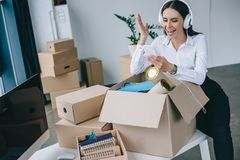 Happy businesswoman in headphones using smartphone while unpacking boxes. In new office royalty free stock photo