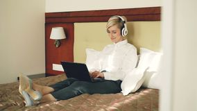 Happy businesswoman in headphones working at laptop computer and listening music smiling dancing while lying in bed at. Happy businesswoman in headphones working stock footage