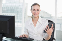 Happy businesswoman holding calculator sitting at desk Stock Photos