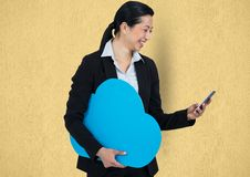 Happy businesswoman holding cloud while using smart phone stock photo