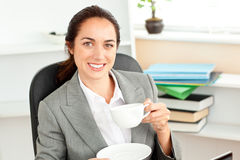 Happy businesswoman holding a coffee in her office Royalty Free Stock Images