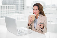 Happy businesswoman holding disposable cup and smartphone Royalty Free Stock Images