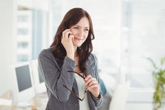 Happy businesswoman holding eyeglasses talking on smartphone Stock Photos