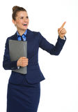 Happy businesswoman holding file, pointing upwards, and smiling Stock Image