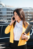 Happy businesswoman holding folder and talking on mobile phone outdoors Royalty Free Stock Images