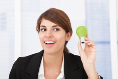 Happy businesswoman holding green light bulb Royalty Free Stock Photo
