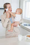 Happy businesswoman holding her baby talking on the phone Royalty Free Stock Photography