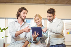 Happy businesswoman holding laptop with colleagues Stock Images