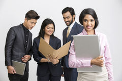 Happy businesswoman holding laptop with her colleagues. Proud businesswoman holding laptop with her colleagues on white background Stock Photos
